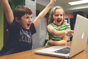 2 students expressiing excitement at a computer screen