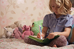A child using C-Pen Reader to read text out loud from a book on her bed. Click to see larger image.
